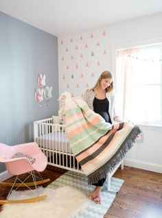 Lula's Baby Bunnyland Nursery Tour | pink chair from Modernica, striped blanket, soft grey wall