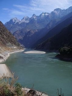 China - Tiger Leaping Gorge  The upstream end, where the wide and peaceful Yangtze is forced into a narrow, angry monster beneath the long, spiked back of the Jade Dragon Mountain.