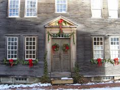 Outside holiday decor with garland strung above the door and over the window boxes