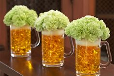 """Great St. Patrick's Day Centerpieces - beer mugs filled with amber gel cubes, round pieces of floral foam for the """"heads"""", topped off with green carnations!"""