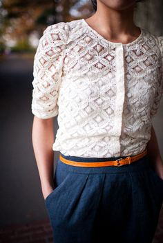 Crocheted blouse with skinny tan belt and blue skirt.