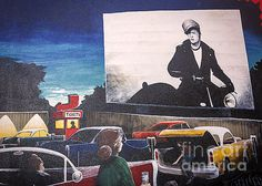 A shot of a mural in Williams, Arizona depicting a Marlon Brando Drive-In Movie.  A drive-in theater is a form of cinema structure consisting of a large outdoor movie screen, a projection booth, a concession stand and a large parking area for automobiles.