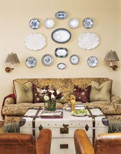 Plate Display:   A collection of transferware plates and platters creates a quirky display above a floral couch. A vintage trunk used as a coffee table and matching wall-mounted lamps add even more personality.