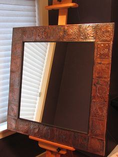 each child would make a square clay tiles....instead of the metal shown in this picture....      kids each get metal square to emboss their pattern and name around mirror. classroom art project to sell at auction mirror, art auction, class projects, school auction, auction idea, clay tiles, art projects, auction projects, kid