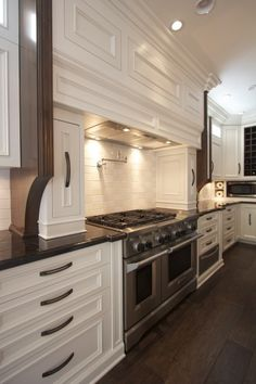 Gorgeous kitchen with creamy white kitchen cabinets with Marron Cohiba Granite countertops, pot filler, subway tiles backsplash and stainless steel warming drawer.