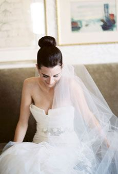 Brides: Wedding Hairstyles that Work Well with Veils  - A Super Sleek High Bun Wedding Hairstyle  The top-knot bun is a great bridal trend as it keeps all eyes on your beautiful face. Pair it with shiny jewelry or keep it simple like this bride with a classic tulle veil.  Brides.com