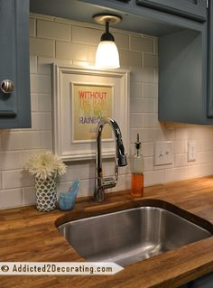 A white subway tile backsplash is a nice contrast to the gray cabinets, butchers block countertop, and stainless Arbor Motionsense faucet.
