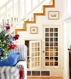 Pretty under stair storage with glass front cabinets.