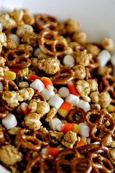 Spooky Trailmix --- 16 oz bag Pretzels, 16 oz bag Peanuts, 18 oz bag Caramel Corn, 12 oz bag Chocolate Chips, 10 oz bag Mini Marshmellows, 2 bags of candy corn.  mix all together, serve in a spooky container.