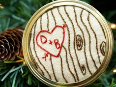 """How clever is this idea!? """"Carve"""" initials onto an embroidery hoop with thread, then attach to a Mason jar lid for a sweet and romantic ornament."""