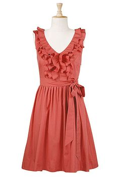 Ruffle front poplin dress with wide V-neck, sash tie at waist, and full, pleated skirt. Can add sleeves, modify dress length, and raise neckline to normal V-neck. Comes in coral, black, dark blue, turquoise, and beige. $60.