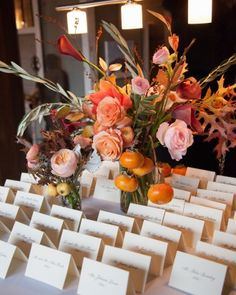 Flower arrangements of orange persimmons and crab apples decorated the escort card table. See more of Hanna and Jimm's Outdoor Fall Wedding in the Hudson Valley on our website!