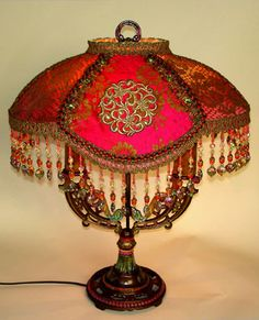 Beautiful old double-arm base is hand painted and crowned by a Tibetan inspired shad which is dyed papaya to deep rose-pink and is covered in both antique gold metallic lace and some incredible fuschia silk damask from the late 1800s. Circular gold metallic appliqués adorn the center panels as well. Colorful hand beaded glass and Swarovski crystal fringe finishes the bottom. This lamps gives off a great warm glow when lit.