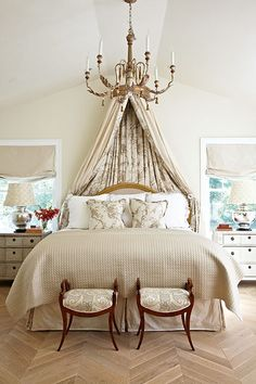 Loving that curtain head board and stools at the foot of the bed.