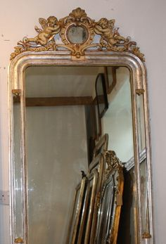 Pair of 19th century arched margin mirrors with etched silver leafed and cream gesso frames and wide cartouches of pair of cherubs each side of central oval glass. Original mirror plates with some age. Also original board backs. Sold as a pair @euroantiques