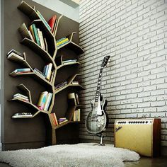 book shelf in the shape of branches; creative way of utilizing the wall space for a mounted bookshelf