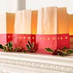 For luminaries,  cut red paper bags in half with decorative scissors, and trip the tops of white of brown bags.  pop out stars with a star-shaped hole punch.  Insert taller bags into red bags; half fill with sand; add LED candles or glass votives.