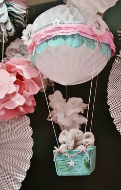 used a Honeycomb Tissue Ball from a large party supply store for the balloon, an empty plastic square container for the basket, along with some fabric, baker's twine, white and pink crepe tissue streamers (also from the party store) ribbon and my glue gun to put it all together.  http://kimemories.typepad.com/celebrate_life/2011/04/project-puffies-hot-air-balloon.html