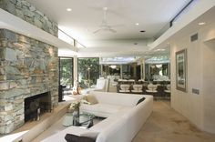Modern living room design with L-shaped white sofa opening up to large rock fireplace.  Adjacent to the living room in an open living style ...