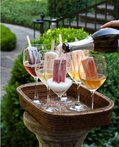 Homemade popsicles submerged in glasses of Prosecco ~ lovely