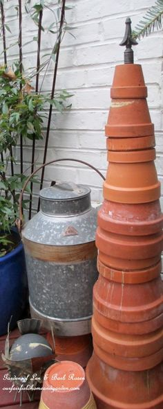 Terracotta tower - one piece of rebar, stacked with terracotta clay pots, topped with a fancy finial...simple country garden art