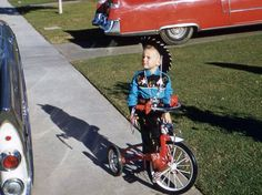 Boomer Cowboy Kid on bike with Caddy in the driveway.