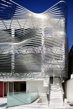 Amano Design Office wraps Tokyo office block with steel ribbons.