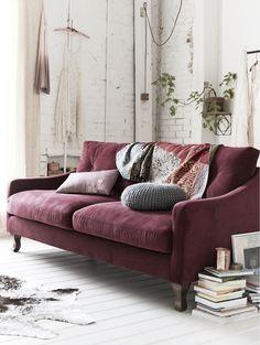 Plum sofa and white brick walls