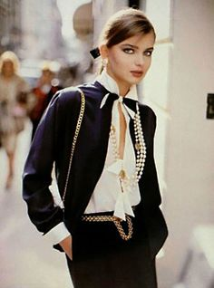Coco Chanel navy suit w/cream blouse & pearls.