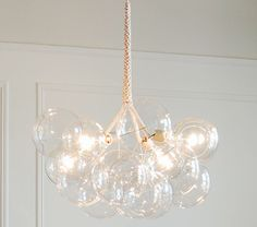 The chandelier is made from 12 hand-blown glass balls and three clear globe lights held together by cables wrapped in cotton twine.