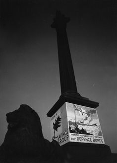 London By Moonlight, 1940, Looking up at Nelson's Column in Trafalgar Square. The plinth is covered with wartime posters advertising Defence Bonds, circa 1940. (Photo by Ministry of Information Photo Division Photographer/ IWM via Getty Images.) #vintage #1940s #WW2