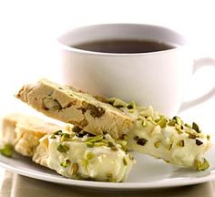 Nutty Biscotti - lemon scented biscotti dipped in lemon white chocolate and sprinkled with chopped macadamias & pistachios.