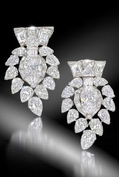 A magnificent pair of diamond clip brooches ~ by Cartier, circa 1935. Each central old pear-shaped diamond, weighing either 4.63 carats or 4.77 carats, Sold for 208,419.