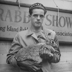 Rabbits  Young man holding his pet rabbit at a rabbit show.  Location:NY, US  Date taken:1943  Photographer:Marie Hansen
