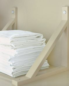 Great Divider  To keep folded linens organized in neat stacks, I flipped two shelf brackets on their heads and fastened them to the wall and the shelf with finish washers. Ekby Valter brackets,