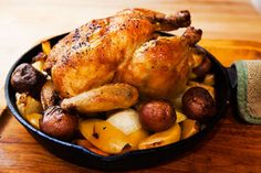 Whole roasted chicken, roasted on a bed of root vegetables in a cast iron pan. Easy one-pan roast chicken dish.