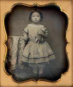 Mitch Young's Collection                                 Spanish Doll Daguerreotype    This is my newest acquisition out of Spain. 1/6th plate daguerreotype of a sweet little girl in her off shoulder dress holding her china head doll. The dress is actually tinted peach and the dolls dress is tinted lilac. Image came in a full case and has old paper seals. The image dates from the early 1850's by the style of the mat. She looks very proud to be holding her doll and did not move a bit which is somewhat rare in children daguerreotypes.
