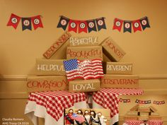 Another pinned said: AHG Ceremonies:This was our picture booth back drop we did to take pictures at are award/crossover ceremony. We used our AHG creed. We wrap the boxes with printed star Kraft wrapping paper. The girls hold a flag sign that said As an American Heritage Girl I promise to be.....
