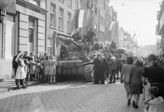 Cheering Dutch civilians gather around a Sherman OP tank of 'C' Troop, 55th Field Regiment RA, Guards Armoured Division, as Eindhoven is liberated, 19 September 1944. Sitting on the front of the tank is Sgt Herbert Frederick Jones.