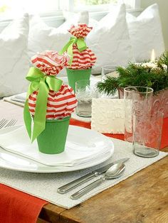 Fun Christmas Favors Inexpensive green peat pots hold handfuls of sweet treats enclosed in candy-cane-stripe tissue paper tied with green satin bows.    #diy #Christmas #crafts