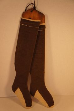 """Antique child's cotton brown and white socks on early wooden sock stretchers. The stretchers are 15"""" long and the socks are 13"""" long.The socks have been on the stretchers for what looks like a long time. The socks had two areas on one sock that has wear holes from being on the stretcher. Both socks and wooden stretchers are 19th C."""