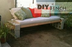 DIY bench. Easy...All you need is four wooden beams and some bricks, all topped with a cushion and fluffy pillows.
