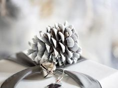 give ordinary pinecones a snowy, frosted look by lightly misting with white spray paint along the entire body. Once dry, layer whitened pinecones onto branches either with rope added as hangers or simply placed loosely throughout the tree.