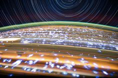 Long-exposure of the earth from the Int'l Space Station. Orange streaks: cities. White blotches: lightning!