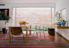 A sala de jantar é banhada por luz natural que entra por um rasgo na parede. O vidro maior é fixo e enquadra os tijolos antigos no muro  Arquivo / Casa e Jardim