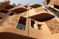 Windows projecting from the facade of residential buildings in Abu Dhabi's Masdar Institute are protected by latticed concrete panels which control interior heat gain and minimize building maintenance.