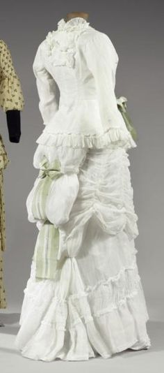 "Bustle dress "" à la Polonaise"" in linen, ca. 1880-85. Two pieces: buttoned bodice with long sleeves and skirt that puffs out in back. Large green and white striped bow in back. costum, summer dresses, vintag fashion, 1880s, green, linens, bows, vintag cloth, basic white"