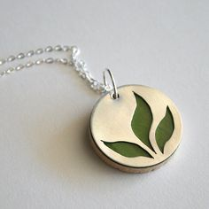 This adorable pendant is handmade from a sterling silver circle with a hand cutout leaves. It hangs in front of a wood circle covered with paper