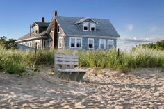 A New England beach cottage that overlooks the dunes and sand.