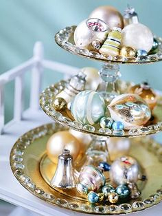Tiered Tray -- Display vintage ornaments by setting them on a tiered serving piece. This one was created using three sizes of silver trays held together by two glasses and wads of florist's clay or museum wax (also known as earthquake wax
